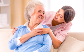 Elderly person and caregiver talking to each other