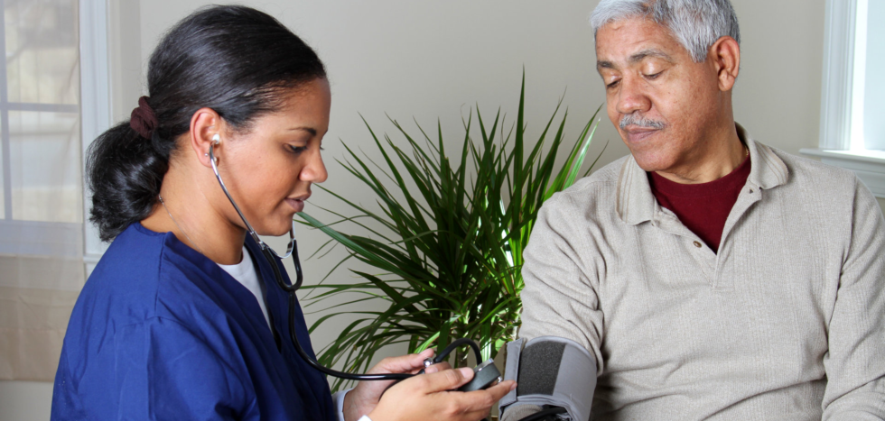 Caregiver checking the blood pressure of an elderly person